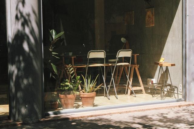 Posuvné sklenené dvere, za ktorými je jedálenský stôl s drevenými stoličkami.jpg