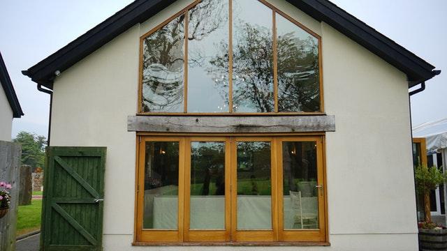Rodinný dom s veľkými oknami a presklenými dverami v drevenom ráme.jpg